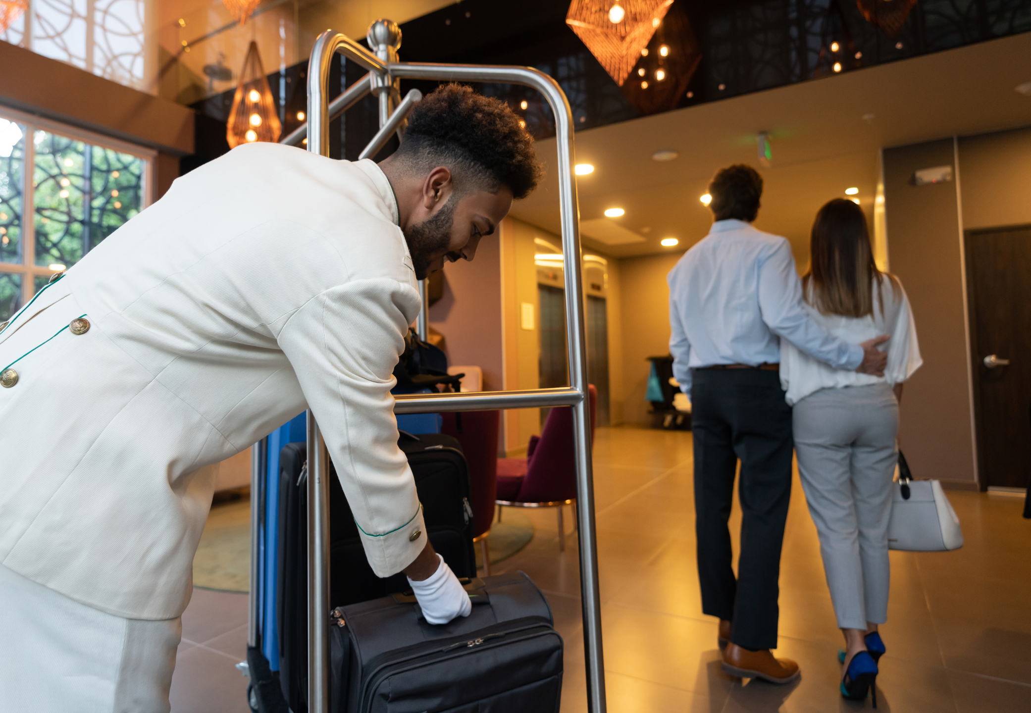 Employee Bellhop Providing Customer Service By Helping Customers With Luggage at a Hotel